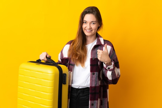 Junge irlandfrau lokalisiert auf gelber wand im urlaub mit reisekoffer und mit daumen nach oben