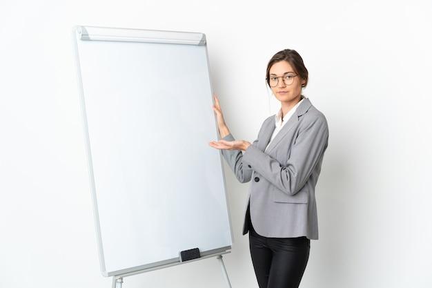 Junge irlandfrau lokalisiert auf weißem hintergrund, der eine präsentation auf weißer tafel gibt