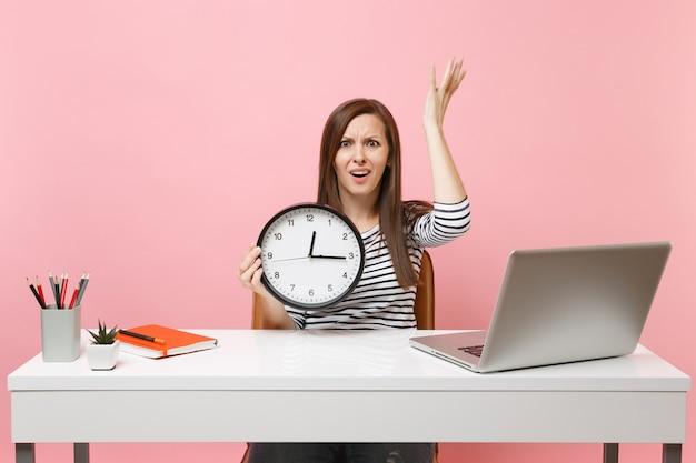 Junge irritierte frau, die hände mit wecker ausbreitet, sitzen, arbeiten im büro mit pc-laptop einzeln auf pastellrosa hintergrund. erfolgsgeschäftskarrierekonzept. platz kopieren. die zeit wird knapp.