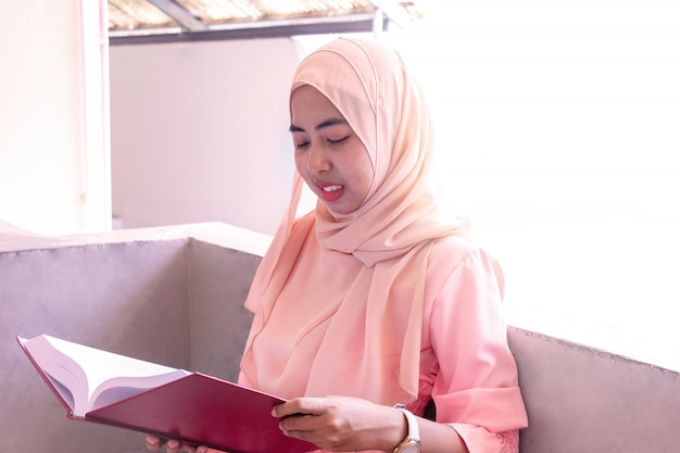 Junge islamische frau sie sitzt und liest ein buch.