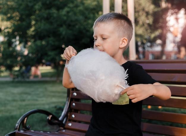 Junge isst die zuckerwatte, die vom klebrigen gesponnenen zucker gemacht wird, der auf einer bank im park sitzt