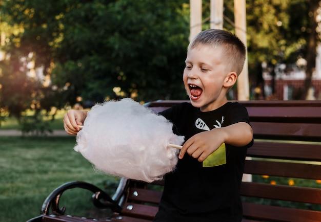 Junge isst mit der vergnügenswatte, die vom klebrigen gesponnenen zucker gemacht wird, der auf einer bank im park sitzt