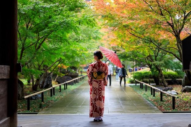 Junge japaner mit rotem kimono und hand mit regenschirm stehen am eingang zum park in der herbstlaubsaison in japan