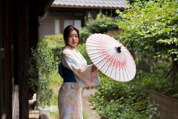 Junge japanerin trägt einen kimono und hält einen regenschirm