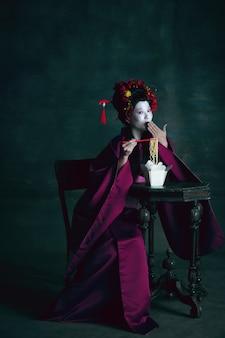 Junge japanische frau als geisha auf dunkelgrünem hintergrund retro-stil vergleich des epochenkonzepts