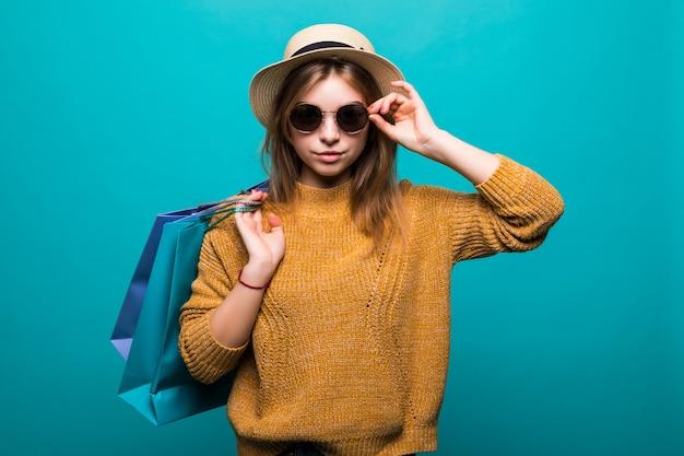 Junge jugendlich frau in der sonnenbrille und im hut, die einkaufstaschen in ihren händen halten, die so glück lokalisiert auf grüner wand fühlen