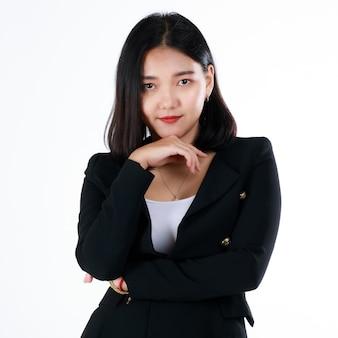 Junge jugendlich frische geschäftsfrau im formellen schwarzen anzug lächelt mit süßem und selbstbewusstem beginn des arbeitslebens im modernen büro. konzept für studienanfänger und den ersten tag der berufslaufbahn.