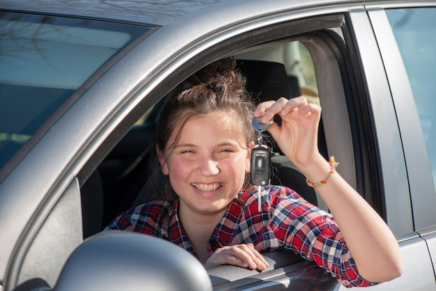 Junge jugendliche, die im auto, schlüssel zeigend sitzt