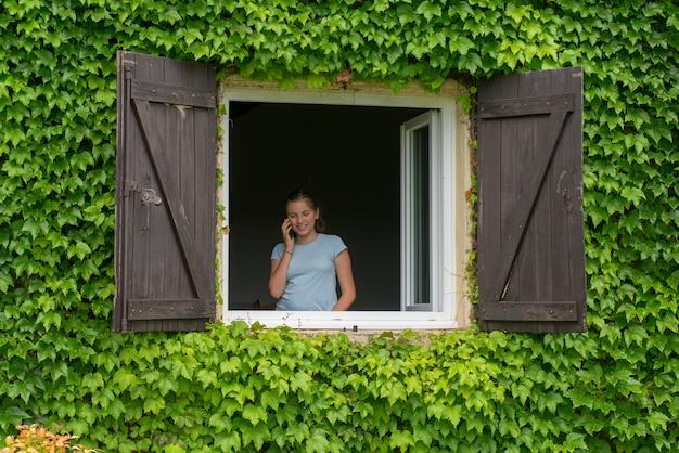 Junge jugendliche nahe dem fenster benutzt einen smartphone