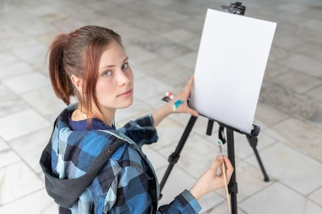 Junge jugendlichkünstlerin mit einem pinsel in ihren händen, die für das malen von ölgemälden sich vorbereiten. auf der schwarzen staffelei befindet sich eine weiße leinwand mit textfreiraum.