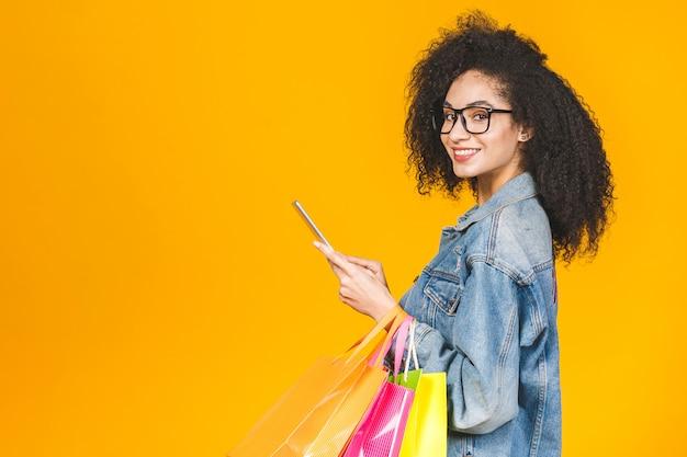 Junge junge afroamerikanerfrau des porträts lächelnd mit bunten einkaufstaschen und tablet-computer lokalisiert über gelbem hintergrund.