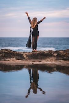 Junge junge brünette kaukasische frau im sommer in einem langen schwarzen transparenten kleid auf einigen felsen nahe dem meer an einem sommernachmittag. arme heben und aufs meer hinausschauen