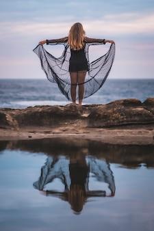 Junge junge brünette kaukasische frau im sommer in einem langen schwarzen transparenten kleid auf einigen felsen nahe dem meer an einem sommernachmittag. im meer reflektiert