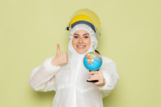 Junge junge frau der vorderansicht im weißen sonderanzug und im gelben helm, der kleinen globus mit leichtem lächeln auf der chemie der grünfläche hält