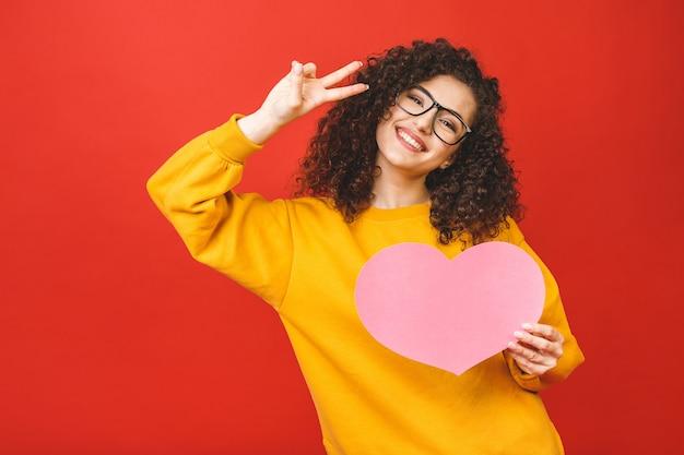 Junge junge frau des fotos, die großes rosa papierherz über rotem farbhintergrund hält.