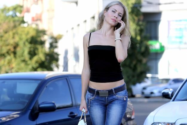 Junge junge frau des geschäfts, die am telefon nahe dem auto spricht