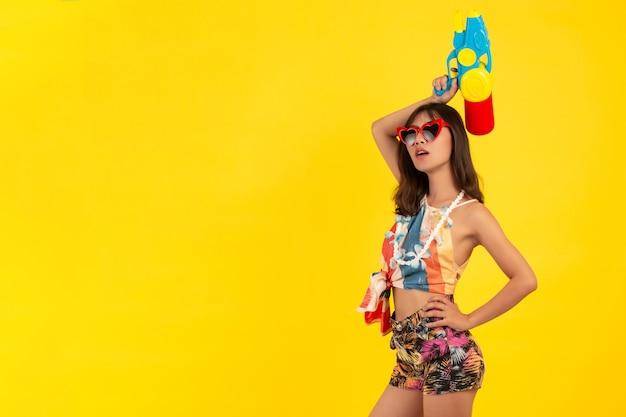 Junge junge schöne frau des sommers mit wasserpistole, songkran-feiertage