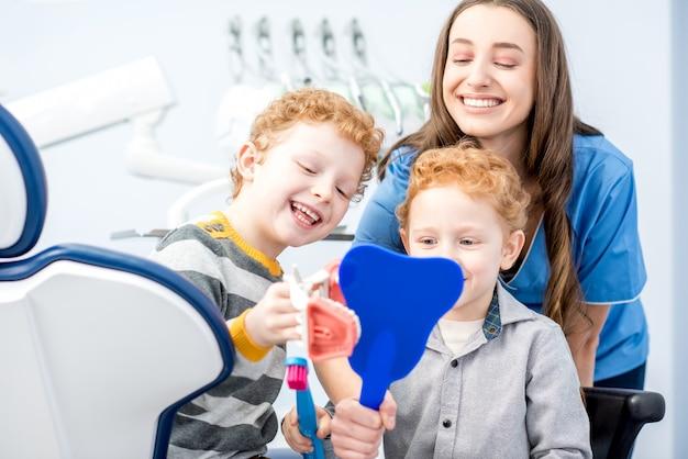 Junge jungen, die mit einem zahnigen lächeln in den spiegel schauen und mit zahnarzt in der zahnarztpraxis sitzen