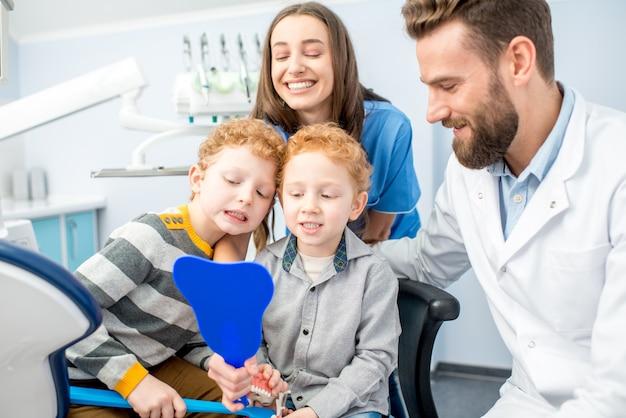 Junge jungen, die mit zahnigem lächeln in den spiegel schauen, sitzen mit zahnarzt und assistentin in der zahnarztpraxis
