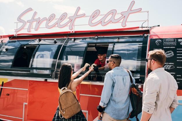 Junge käuferin, die zwei hotdogs im imbisswagen nimmt