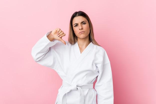 Junge karatefrau, die eine abneigungsgeste, daumen unten zeigt. uneinigkeit konzept.