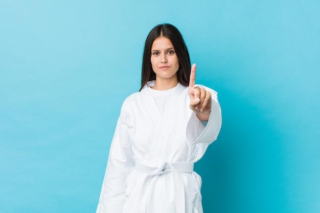 Junge karatefrau, die nummer eins mit dem finger zeigt.