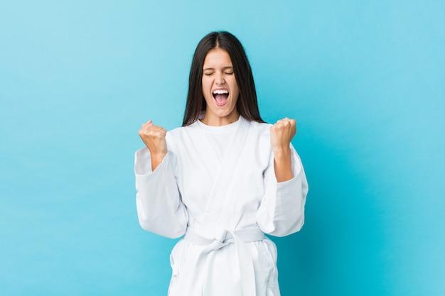 Junge karatefrau, die sorglos und aufgeregt zujubelt