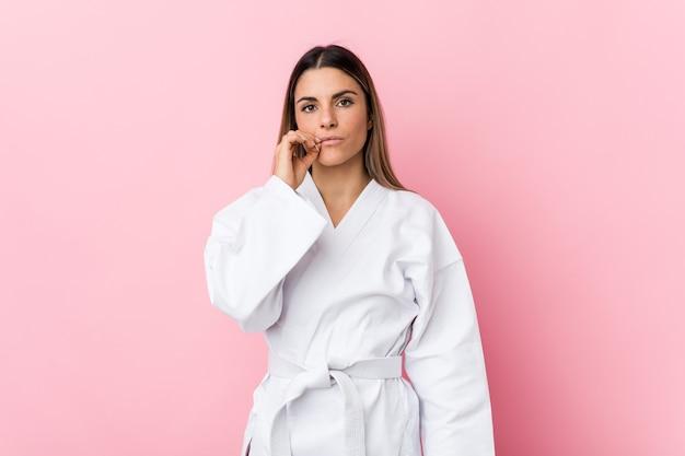 Junge karatefrau mit den fingern auf den lippen, die ein geheimnis halten.