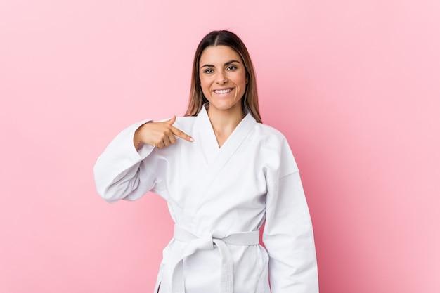 Junge karatefrauenperson, die eigenhändig auf einen hemdkopienraum, stolz und überzeugt zeigt