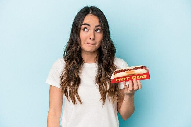 Junge kaukasierin, die einen hotdog einzeln auf blauem hintergrund hält, verwirrt, fühlt sich zweifelhaft und unsicher.