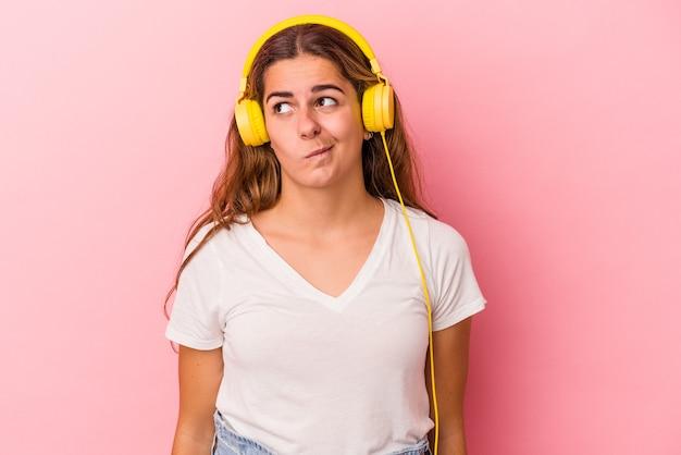 Junge kaukasierin, die musik einzeln auf rosafarbenem hintergrund hört, verwirrt, fühlt sich zweifelhaft und unsicher.