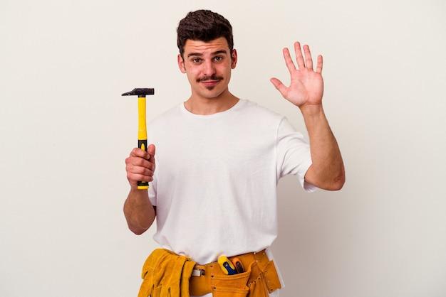Junge kaukasische arbeiter mann mit werkzeugen isoliert auf weißem hintergrund lächelnd fröhlich zeigt nummer fünf mit fingern.