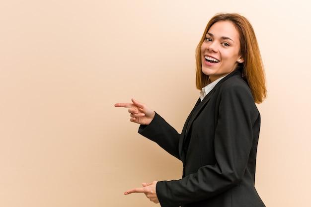 Junge kaukasische aufgeregte geschäftsfrau, die mit den zeigefingern weg zeigt.