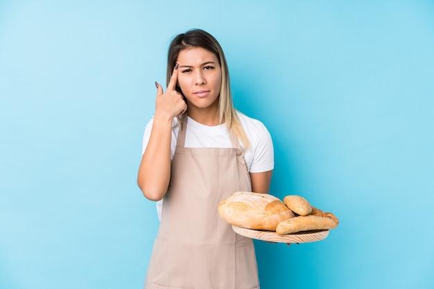 Junge kaukasische bäckerfrau lokalisiert, eine enttäuschungsgeste mit dem zeigefinger zeigend.