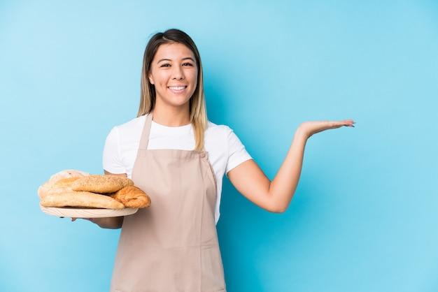 Junge kaukasische bäckerfrau lokalisiert, einen kopienraum auf einer palme zeigend und eine andere hand auf taille halten.