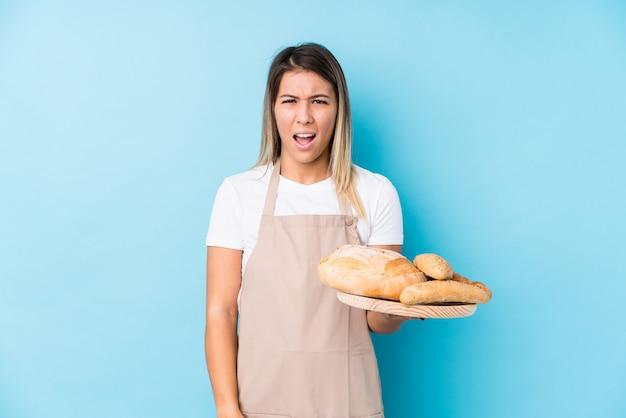 Junge kaukasische bäckerfrau lokalisiert sehr verärgert und aggressiv schreiend.