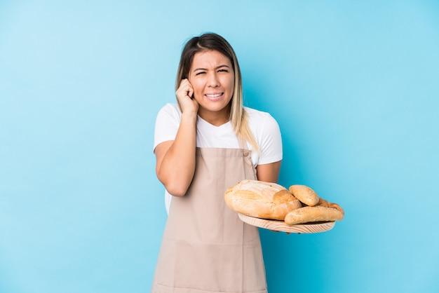 Junge kaukasische bäckerfrau lokalisierte bedeckungsohren mit den händen.