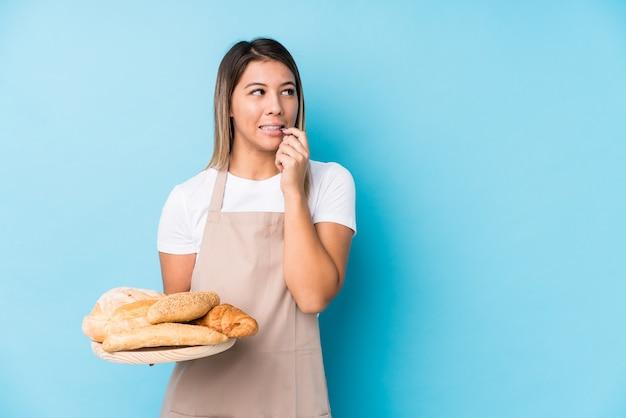 Junge kaukasische bäckerfrau lokalisierte das entspannte denken an etwas, das einen kopienraum betrachtet.