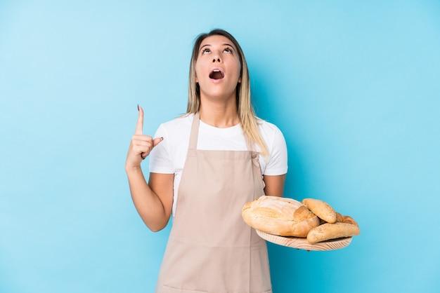 Junge kaukasische bäckerfrau trennte das zeigen der oberseite mit geöffnetem mund.