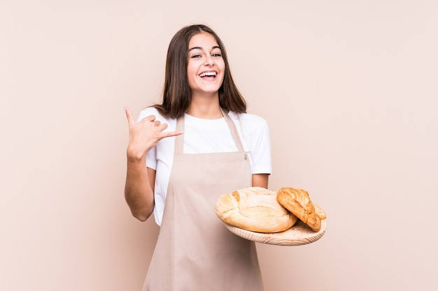 Junge kaukasische bäckerin lokalisiert, die eine handy-anrufgeste mit fingern zeigt.