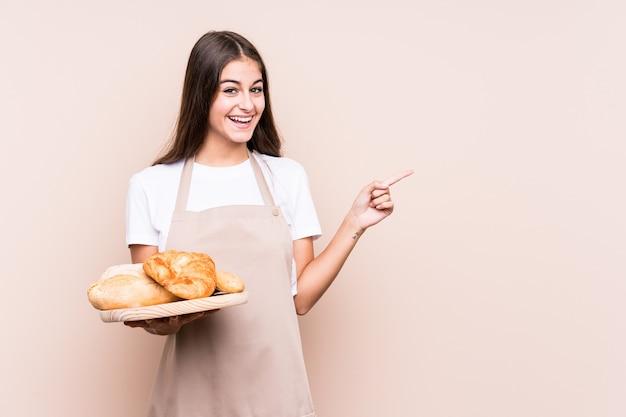 Junge kaukasische bäckerin lokalisiert lächelnd und beiseite zeigend, etwas an der leeren stelle zeigend.