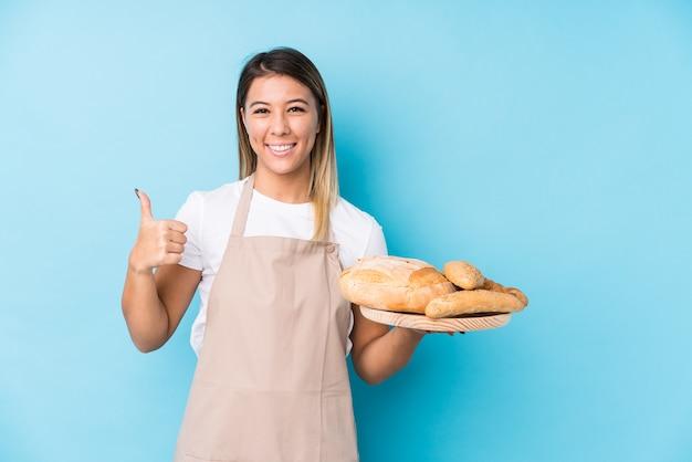 Junge kaukasische bäckerin lokalisiert lächelnd und daumen hochhebend