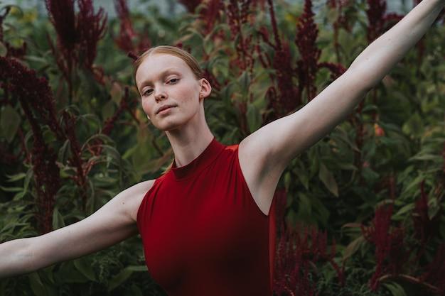 Junge kaukasische balletttänzerin, die im burgunderfarbenen kostüm aufwirft