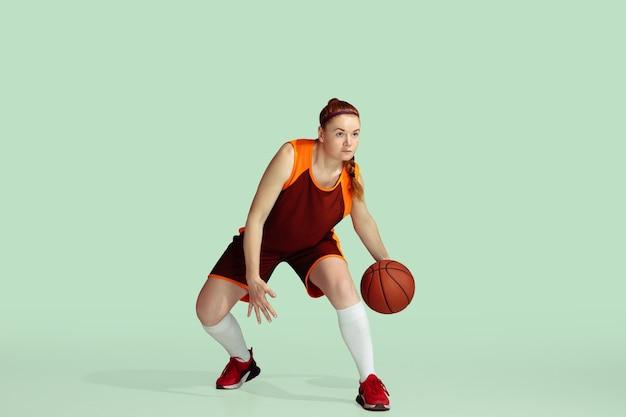Junge kaukasische basketballspielerin in aktion, bewegung während des spiels auf mintfarbenem hintergrund isoliert. konzept von sport, bewegung, energie und dynamischem, gesundem lebensstil. trainieren, üben.