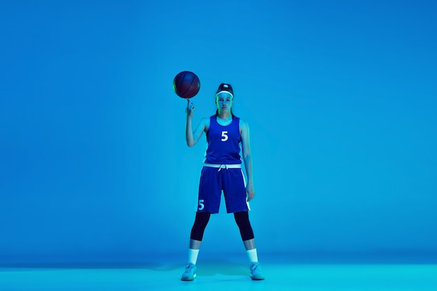 Junge kaukasische basketballspielerin isoliert auf blau im neonlicht