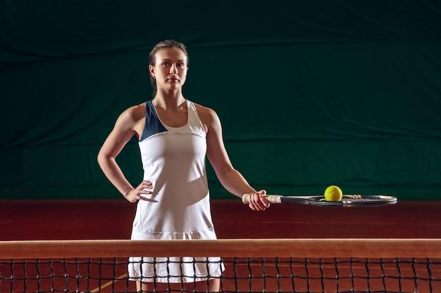 Junge kaukasische berufssportlerin, die tennis auf sportplatzwand spielt.