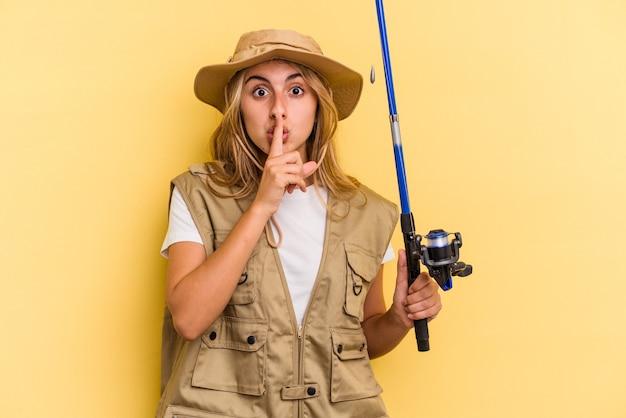 Junge kaukasische blonde fischerin, die eine stange auf gelbem hintergrund hält, die ein geheimnis hält oder um stille bittet.