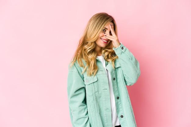 Junge kaukasische blonde frau blinzeln durch finger, verlegenes bedeckendes gesicht.