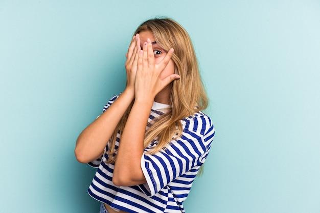Junge kaukasische blonde frau, die auf blauem hintergrund isoliert ist, blinzelt erschrocken und nervös durch die finger.