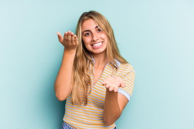 Junge kaukasische blonde frau, die auf blauem hintergrund isoliert ist, macht skala mit armen, fühlt sich glücklich und selbstbewusst.